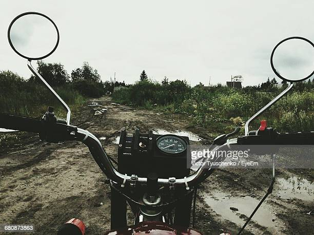 motorcycle on muddy field against sky - handlebar stock photos and pictures