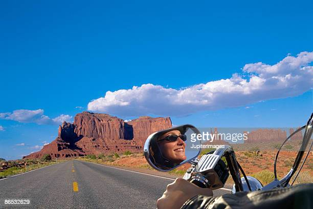 motorcycle on rural road in monument valley - monument valley stock-fotos und bilder