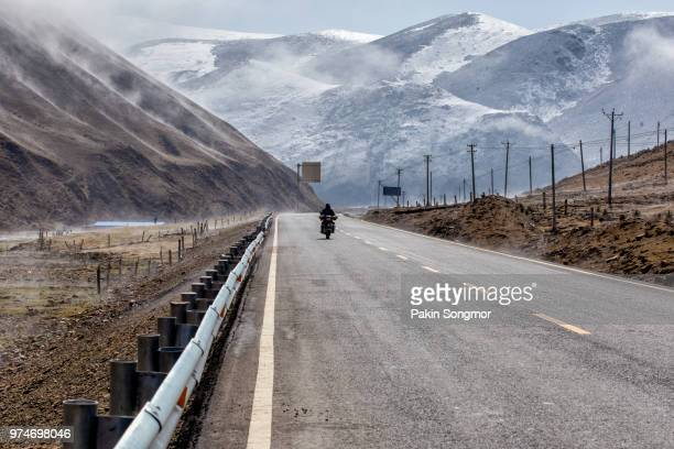 Motorcycle on the road, Beautiful winter road in Tibet under snow mountain Sichuan