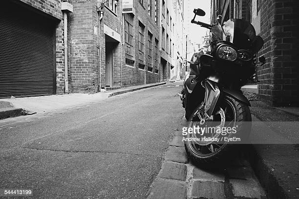 Motorcycle Parked On Empty Street Amidst Buildings In City