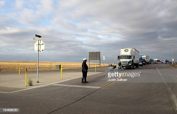 A motorcycle police officer blocks traffic as the motorcade of Republican presidential candidate Mitt Romney passes by on October 24 2012 in Denver...