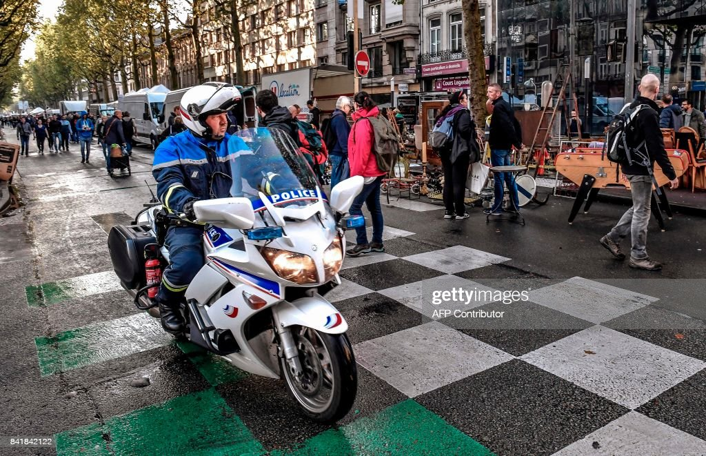 A motorcycle police officer rides past stalls at the Braderie de ...