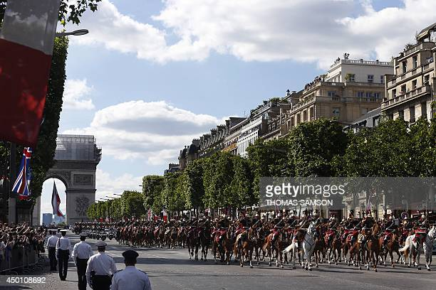 Motorcycle policemen escort the car carrying Britain's Queen Elizabeth II and French President Francois Hollande as it drives down the ChampsElysees...
