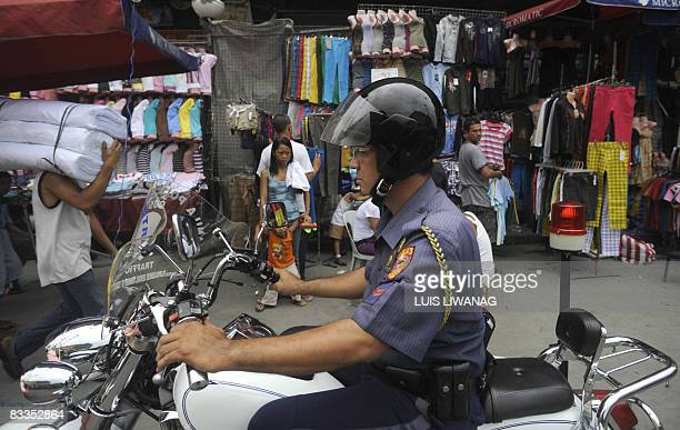 A motorcycle policman patrols a hawkers street market at the Divisoria market in Manila on October 20 2008 Rising cost of fuel and basic commodities...