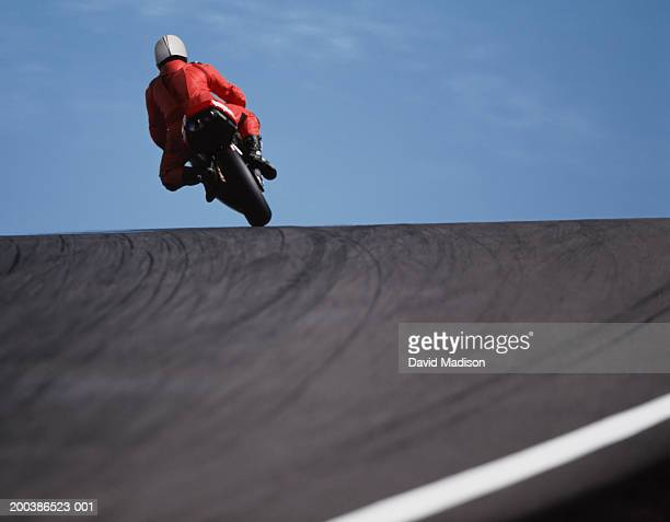 Motorcycle racer cresting hill, rear view, low angle view
