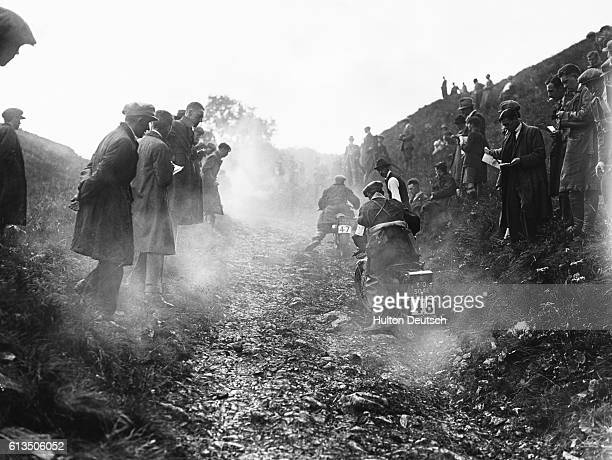 Motorcycle racers struggle up a hill during the second day of competition in the Auto Cycle Union Six Day Trials at Blackwell Heath.
