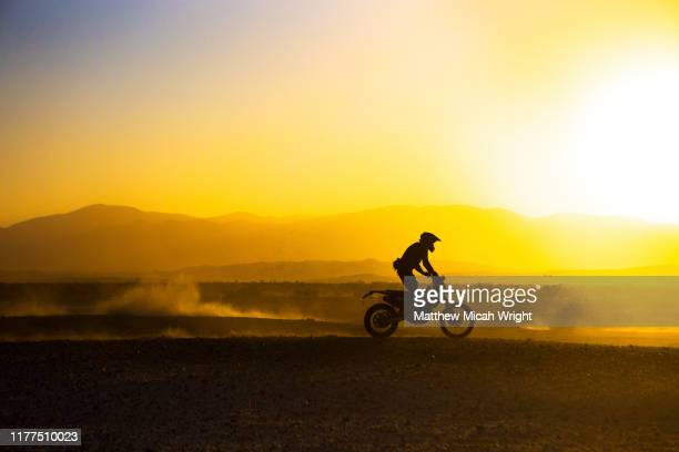 a motorcycle races through the desert. - motorcycle racing stock pictures, royalty-free photos & images