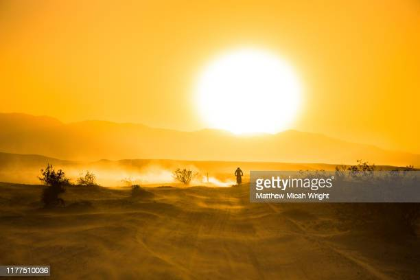 a motorcycle races through the desert. - man made space stock pictures, royalty-free photos & images