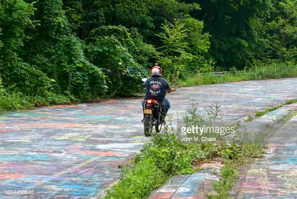 """motorcycle rider on """"graffiti road"""" - centralia pennsylvania foto e immagini stock"""