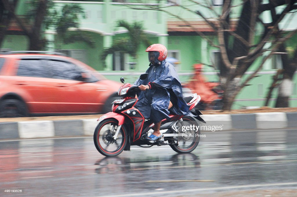 Motorcycle rider wears a poncho to cover himself from the... : News Photo