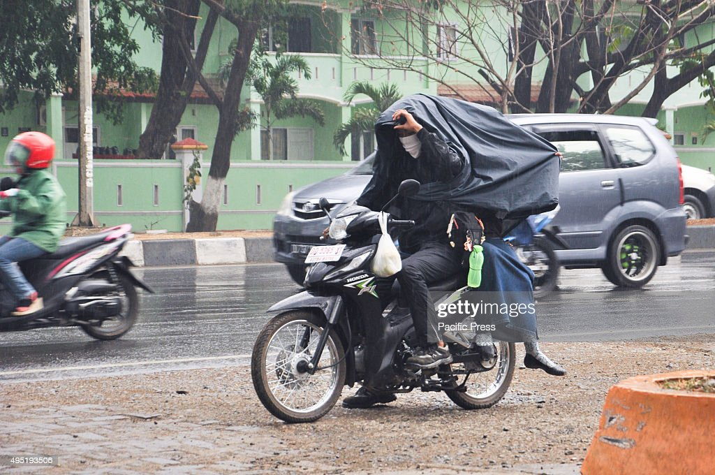 Motorcycle riders try to cover themself from rain in Kapasa... : News Photo