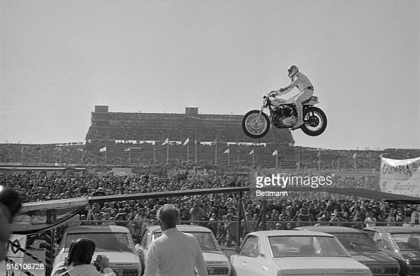 Motorcycle stunt man Evel Knievel sails over a line of 19 automobiles in a record breaking effort before the start of the Miller 500 stock car race...