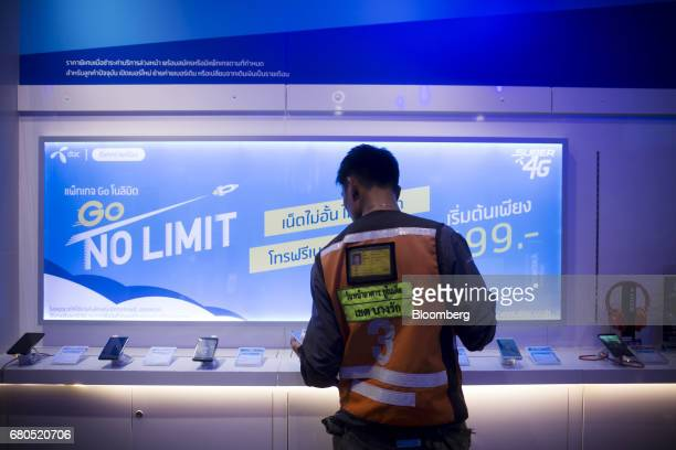 A motorcycle taxi driver browses smartphones inside a Total Access Communication Pcl store in Bangkok Thailand on Wednesday May 3 2017 Thailand's...