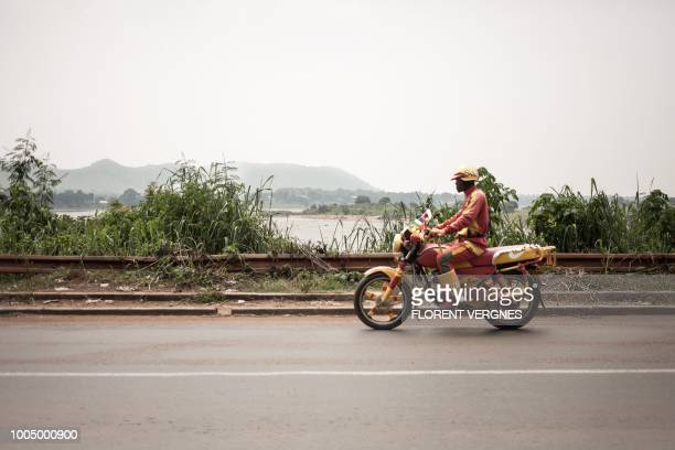 A motorcycle taxi driver rides on July 21 along a road from Ngaragba in Bangui Since the beginning of July a decree has been passed prohibiting...