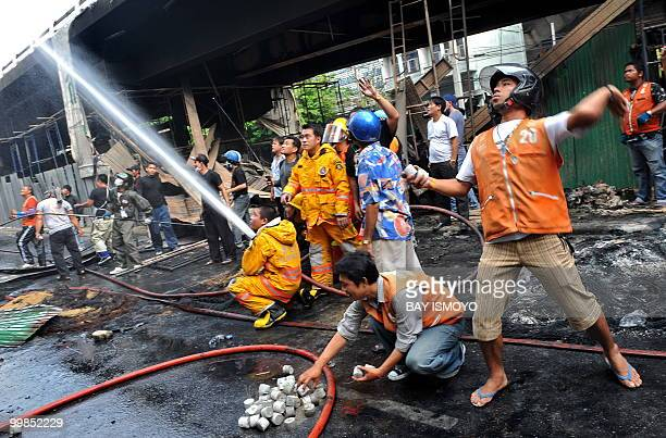 A motorcycle taxi driver throws stones to break the glass panes of a building on fire to allow firefighters to douse the flames as firefighters use a...