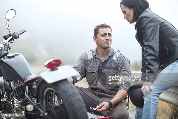 motorcycle technician helping stranded biker with broken bike - motorcycle accident stock pictures, royalty-free photos & images