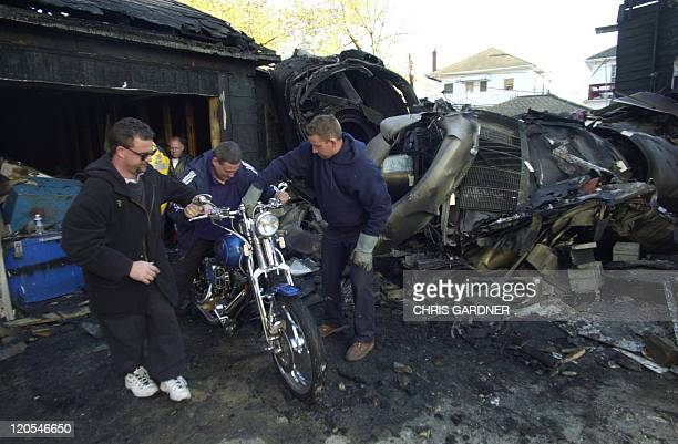 A motorcycle that sustained little damage is rescued from a garage 13 November where the remains of an engine from American Airlines Flight 587...