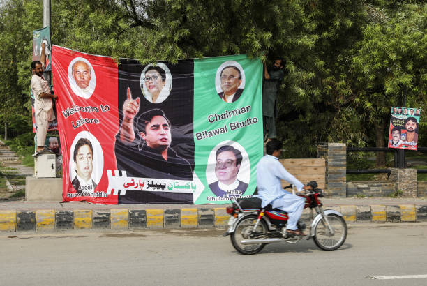 A motorcycle travels along a road as workers hang a campaign banner for the Pakistan Peoples Party in Lahore Pakistan on Thursday July 17 2018...