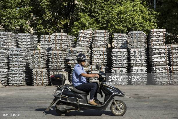 A motorcycle travels along a road next to bundles of aluminum ingots sitting stacked on the side of a road near a China National Materials Storage...