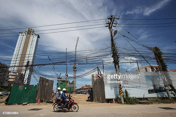 A motorcycle travels past cranes operating on the construction site of the Veranda Residence Pattaya developed by Veranda Group in the Na Jomtien...