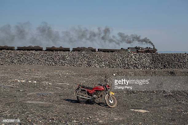 A motorcycle waits on the highland for its owner a railway worker After the steam train dumps the coal cinders the worker will finish his work and go...
