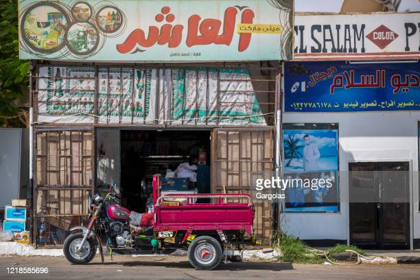 motorcycle with cart park in front of a convenience store, aswan, egypt - poor service delivery stock pictures, royalty-free photos & images