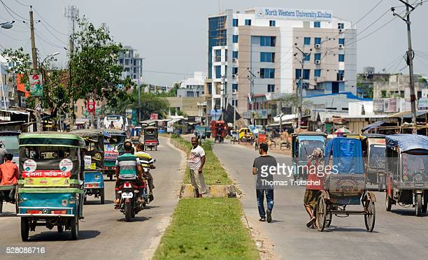 Motorcycles and rickshaws drive on the street on April 11 2016 in Khulna Bangladesh