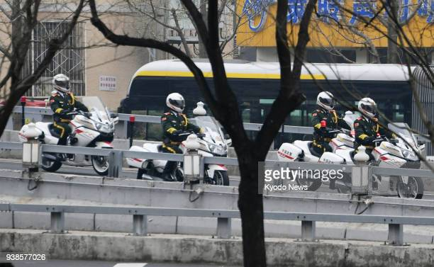 Motorcycles escort a motorcade believed to be carrying a highranking North Korean official to Beijing train station from the Diaoyutai State...
