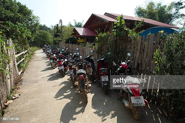 Motorcycles park outside on a narrow lane during ceremonies at the wedding of Kanokporn and Montri Thi in Ta Par Mok Thailand Thai Buddhist marriage...