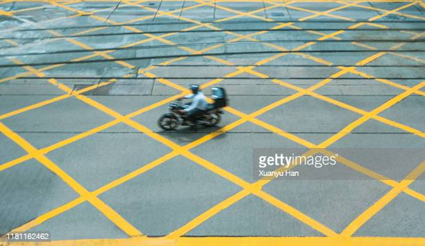 motorcycles passing through an empty intersection in hong kong - walk don't walk signal stock pictures, royalty-free photos & images