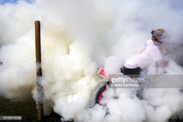 TOPSHOT A motorcycling enthousiast produces smoke with his bike as fans gather at the camp site at the eyetime MotoGP in Austria on August 11 in...