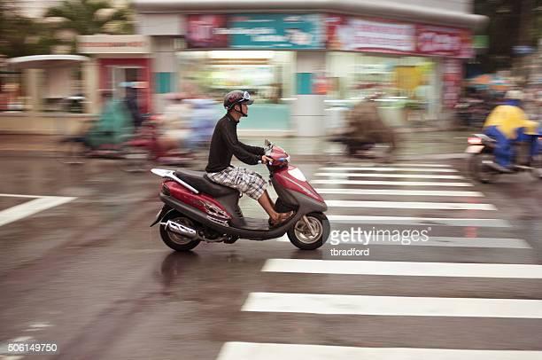 Motorcycling através de uma tempestade no Vietname