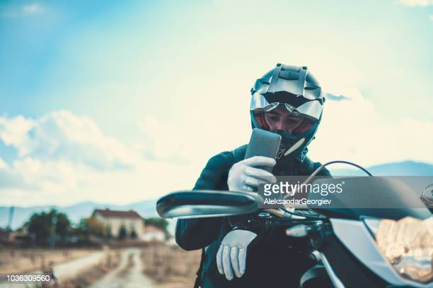 motorcyclist adjusting the navigation on mobile phone on lake side - motorcycle racing stock pictures, royalty-free photos & images