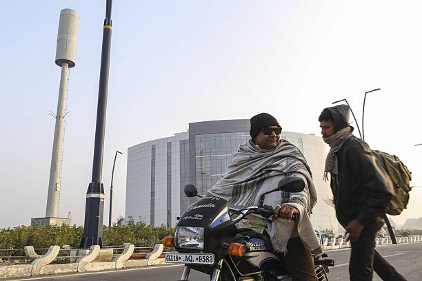 General views of the under construction tec city a motorcyclist and a pedestrian stand near a commercial building in gujarat international finance tec negle