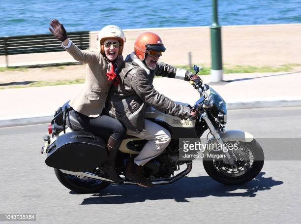 A motorcyclist and his passenger smile and wave during a charity ride on September 30 2018 in Sydney Australia The Distinguished Gentleman's Ride is...