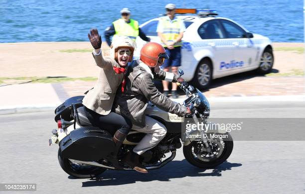A motorcyclist and his passenger wave and smile as they pass two police officers during a charity ride on September 30 2018 in Sydney Australia The...