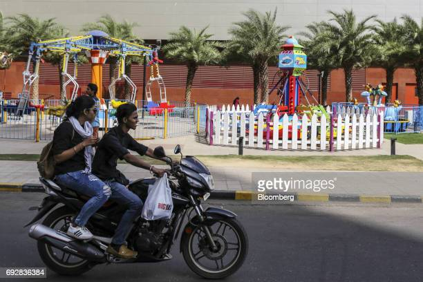 A motorcyclist and passenger ride past a playground outside the Xperia Mall in Palava City on the outskirts of Mumbai India on Thursday May 25 2017...