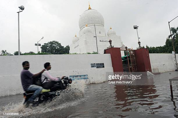 A motorcyclist and pillion rider drive through the flooded Syedna Qutbuddin Shahid RA Roza street also known as Bohra No Rojo in the Saraspur area of...