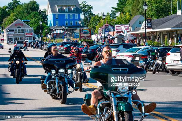 Motorcyclist and tourist cruise and walk the boardwalk along Lake Winnipesaukee at Weirs Beach during the 97th annual Laconia Bike Week in Laconia,...