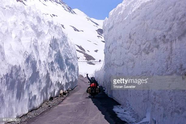 Motorcyclist between high snow walls near Baralacha pass on the Manali-Leh highway. Bara-lacha la also known as Bara-lacha Pass is a high mountain...
