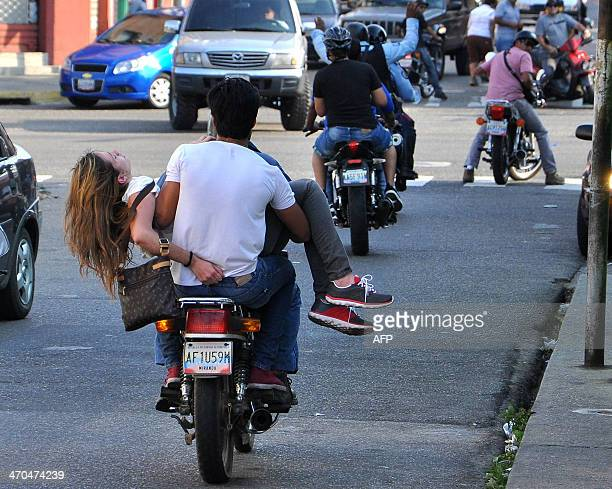 A motorcyclist carries Venezuelan model Genesis Carmona injured during an antigovernment protest in Valencia on February 18 2014 The 21yearold model...