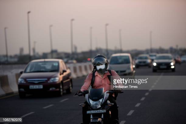 A motorcyclist covers his face to protect himself from the pollution on October 22 2018 in New Delhi India Air pollution continues to be above...