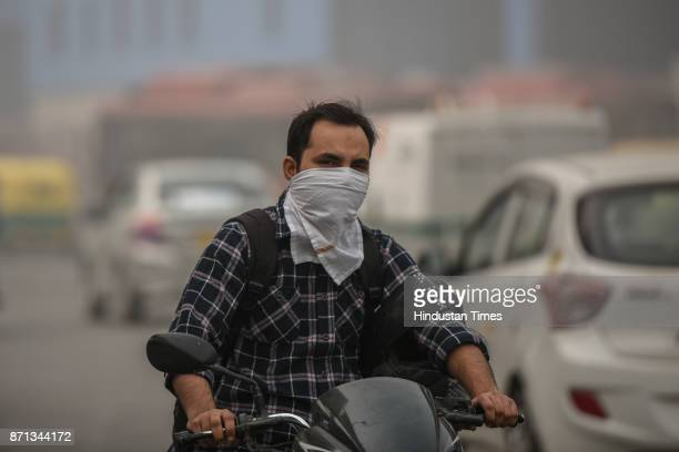A motorcyclist covers his face with a handkerchief to avoid smog on a hazy morning on November 7 2017 in New Delhi India Delhi woke up to a thick...