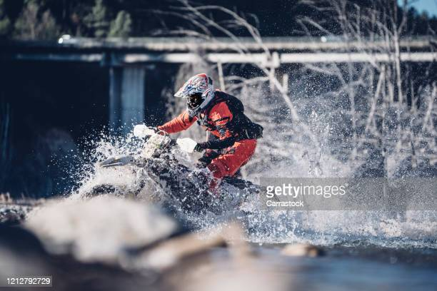 motorcyclist crosses a river with motocross motorcycle - motorsport stock pictures, royalty-free photos & images