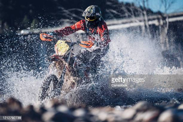 motorcyclist crosses a river with motocross motorcycle - オートバイ競技 ストックフォトと画像