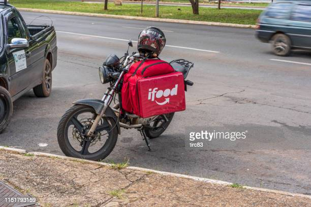 motorcyclist delivering fast food - distrito federal brasilia stock pictures, royalty-free photos & images