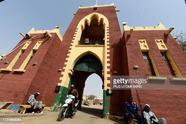 A motorcyclist drives away from the palace of the Emir of Kano Sanusi Lamido Sanusi in Kano on February 14 2019 The artistic framework projects...