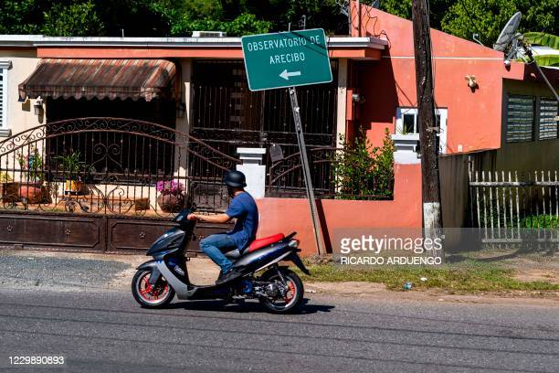 Motorcyclist drives by a road sign towards the Arecibo Observatory in Arecibo, Puerto Rico on December 1, 2020. - The Arecibo Observatory telescope...