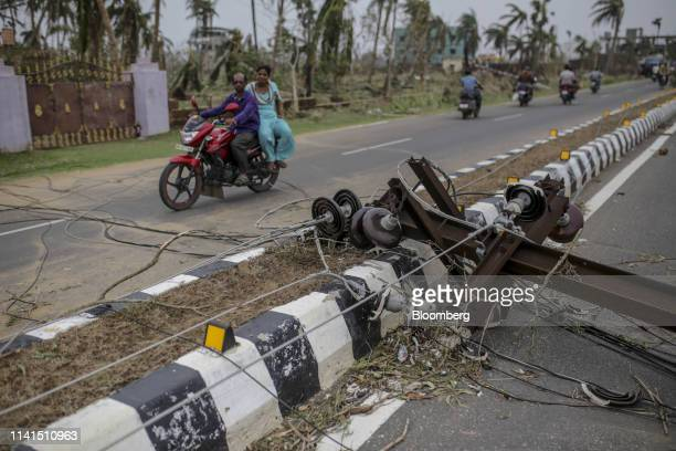 A motorcyclist drives past a damaged electrical pole in Puri Odisha India on Sunday May 5 2019 Authorities launched a massive restorationandrelief...