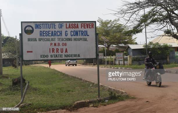 A motorcyclist drives past a street sign for the Institute of Lassa Fever Research and Control in Irrua Specialist Teaching Hospital in Irrua Edo...